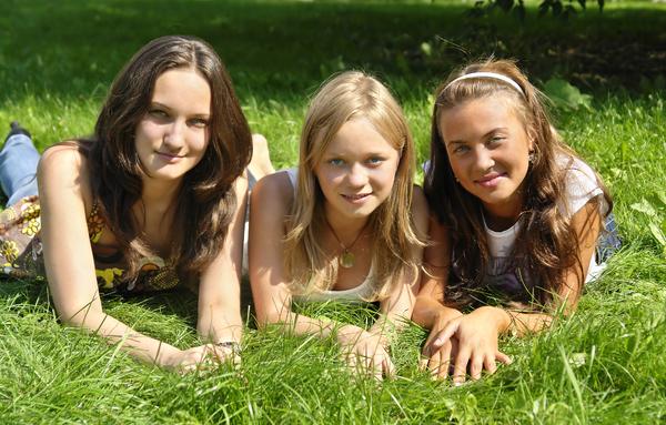 Tytöt makoilevat kesäisellä ruohikolla
