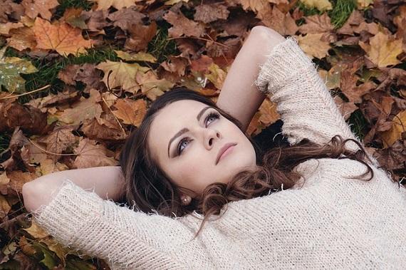 Kuvassa tyttö lepäilee syksyisessä lehtikasassa