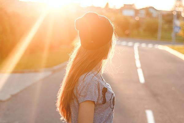 Nuori nainen sivuprofiilissa katsoo kohti auringonlaskua.