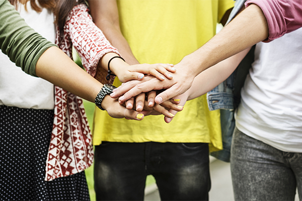 Kolme nuorta pitää käsiä päällekkäin, yhdellä on keltainen paita, yhdellä kuviollinen ja yhden paitaa ei näy.