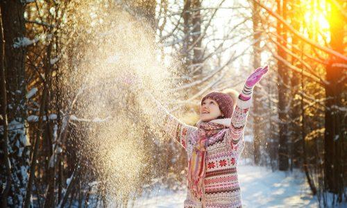 Kuvassa nainen heittää lunta ilmaan. Aurinko paistaa.