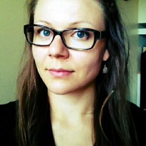 Kuvassa nuori nainen. Ruskea pitkä tukka. Silmälasit. Hymyilee.