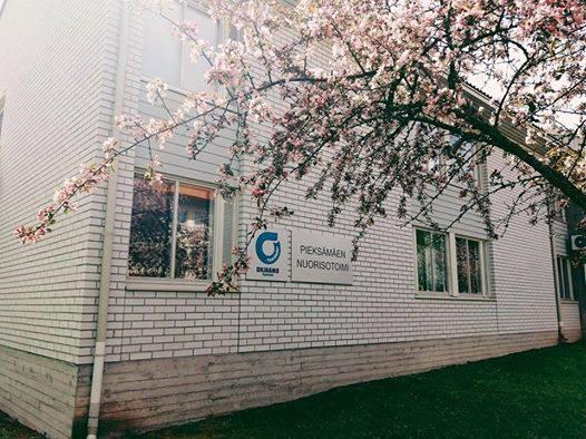 Ohjaamo Pientareen rakennus. Valkoinen tiilitalo. Ohjaamon logo seinässä. Edustalla puu, jossa vaaleanpunaisia kukkia.
