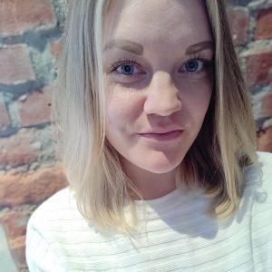 Kuvassa nuori nainen. Vaalea hartioille ylettyvä tukka. Valkoinen paita. Hymyilee kuvassa.