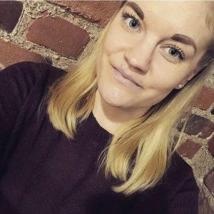 Kuvassa nuori nainen. Vaaleat hiukset, Hieman meikkiä. Hymyilee kuvassa. Taustalla tiiliseinä