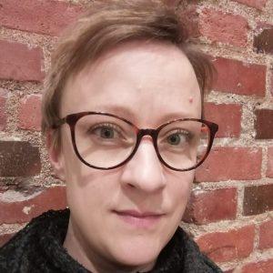 Kuvassa aikuinen vaalea nainen. Tummasankaiset silmälasit. Lyhyt vaaleahko tukka kammattuna sivulle. Taustalla tiiliseinä