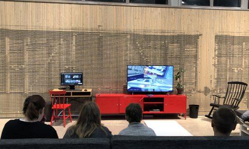 Nuoria katsomassa telkkaria nuorisotila Weturissa. Kolme nuorta, TV, punainen tv-taso