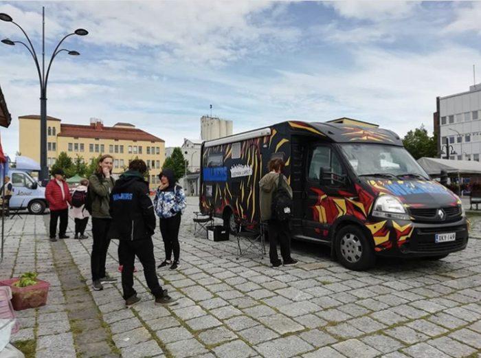 Wauto-auto Pieksämäen kauppatorilla. Kuvassa on Wauto ja nuoria. Taustalla kauppatori