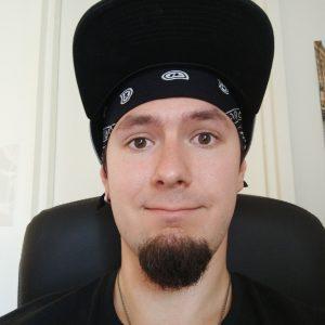 Hymyilevä nuori mies. Musta pukin parta. Lippalakki päässä.