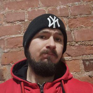 Kuvassa nuorimies pipopäässä. Musta paksu parta. musta pipo ja punainen huppari. Taustalla tiiliseinä.