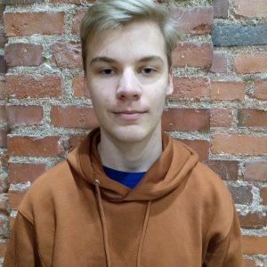 Kuvassa vaalea nuori mies. Blondi lyhyt tukka kammattuna sivulle. Ruskea huppari.