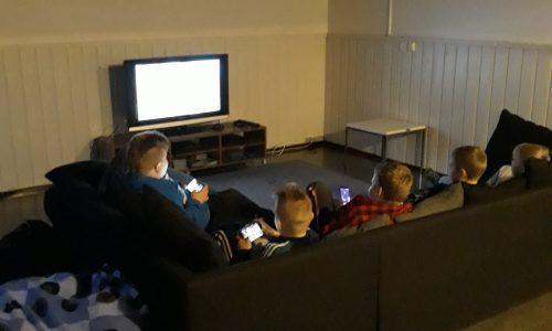 Nuorisotila Virnun lapsia katsomassa TV:tä. Valkoinen seinä, harmaa kulmasohva, viiden lapsen takaraivot