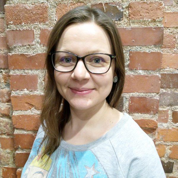 Kuvassa aikuinen nainen. Maantien ruskea keskipitkä tukka. Tumma sankaiset silmälasit, Harmaa college paita. Hymyilee. Taustalla tiiliseinä