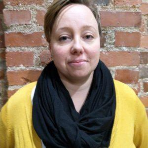 Kuvassa vaalea nainen, lyhyet maantien väriset hiukset. Musta huivi kaulassa ja keltainen villatakki. Taustalle tiiliseinä.