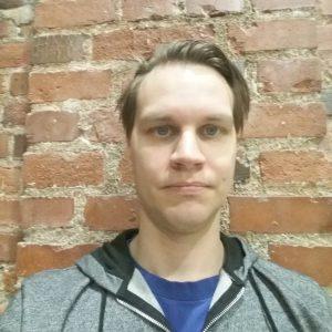 Kuvassa vaalea mies. Harmaahuppari. Taustalle tiiliseinä. Lyhyt tukka kammattu sivulle