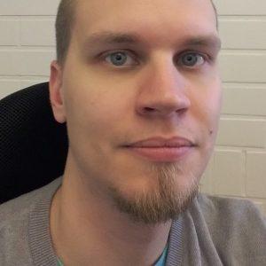 Vaalea hymyilevä mies. Lyhyt siilitukka. Pieni parta.