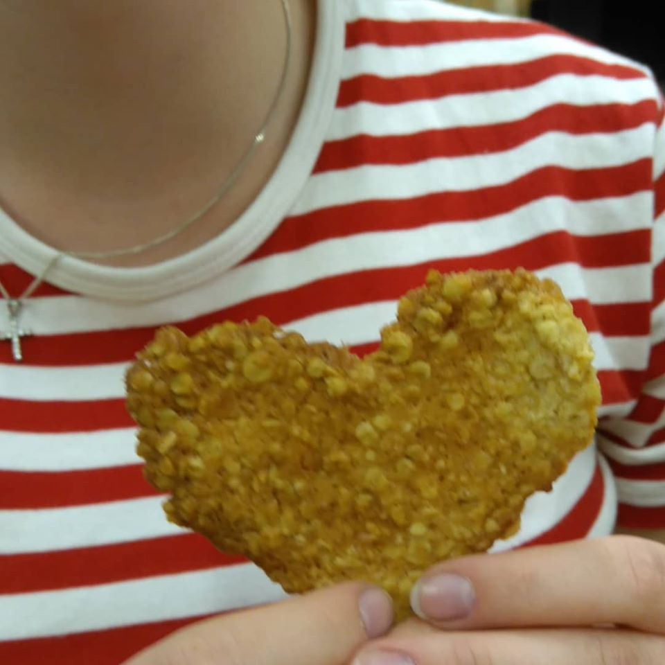 tytön käsissä pitämästä kaurakeksistä, joka on sydämenmuotoinen