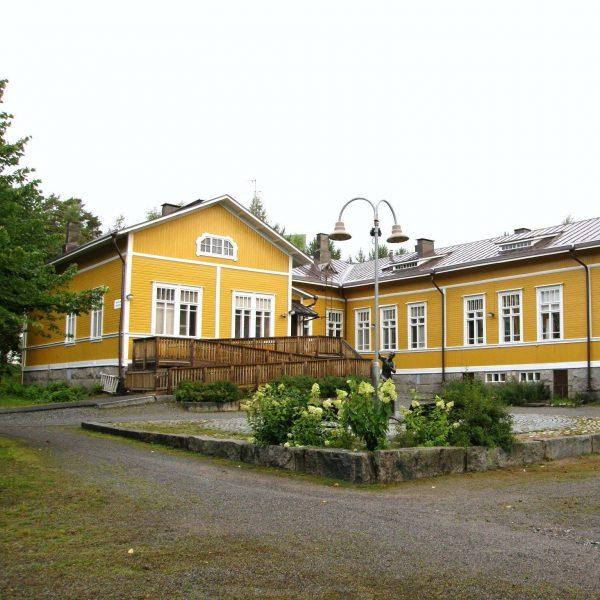Kuvassa männistön nuorisotila latari. Rakennus on vanha puurakennus ja maalattu keltaiseksi. Kuvassa näkyy latarin sisäänkäynti, minne johtaa portaat, sekä pyörätuoli liuska.