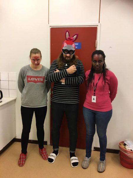Kolme henkilöä seisoo rivissä naamiaisasuissa.