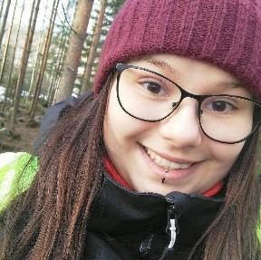 Kuvassa Majakan nuorisonohjaaja Sanna Pitkänen, hänellä on ruskeat pitkät hiukset, punainen pipo ja mustasankaiset silmälasit kuvassa