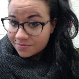 Musta hiuksinen nuori nainen hymyile kuvassa. Huulilävistys ja silmälasit