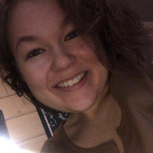 Nuorisovaltuusto piston jäsen Karoliina Tyrväinen. Lyhyt ruskea tukka, hymyilee kuvassa.