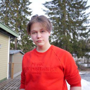 Nuorisovaltuusto Piston jäsen Sara Hynninen. Lyhyt ruskea tukka, keskijakaus. Punainen huppari. Taustalla luminen piha.