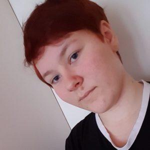 Kuvassa nuorisovaltuusto Piston jäsen Sonja Koskinen. Lyhyt punainen tukka. Ei meikkiä. Musta paita, hymyilee hieman
