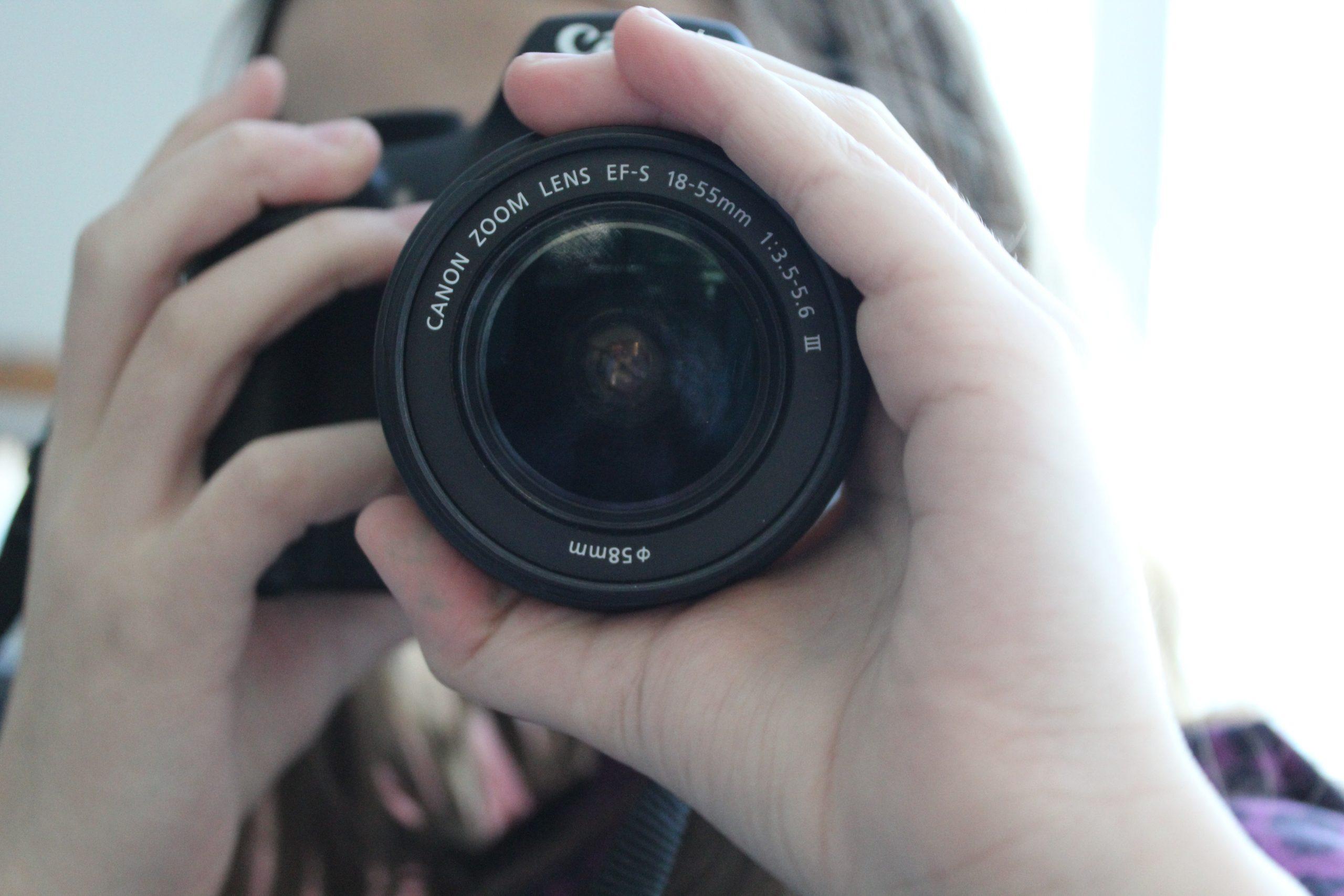 Nuori ottamassa valokuvaa järjestelmäkameralla