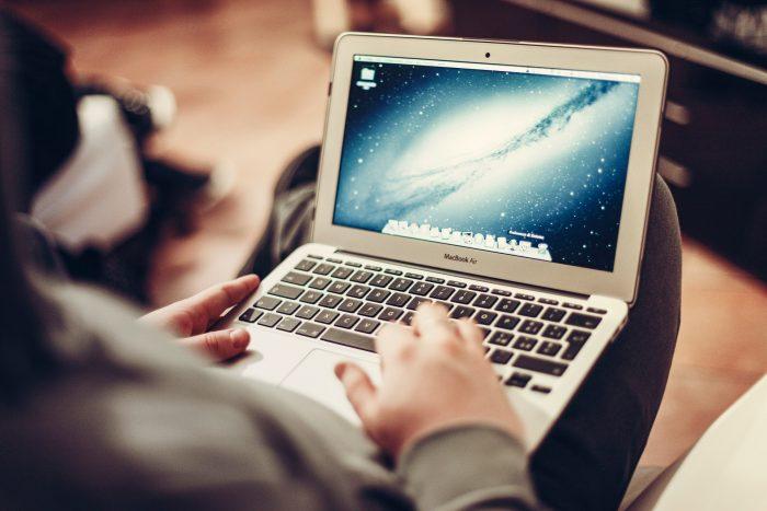 kannettava tietokone ihmisen sylissä