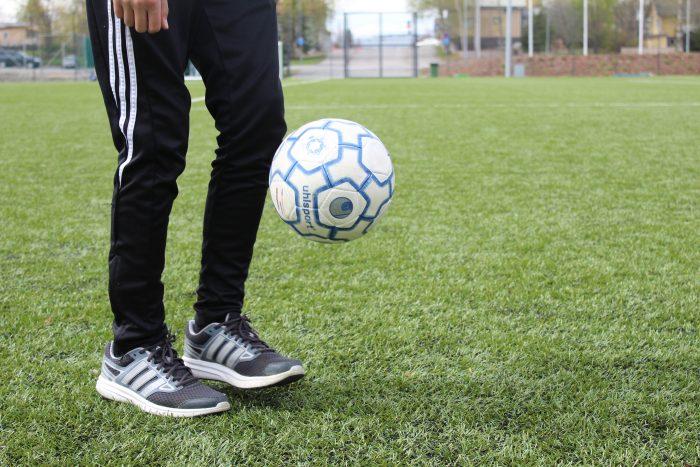 Nuori pomputtelee jalkapalloa tekonurmikentällä