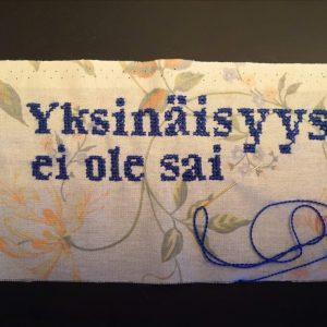 """Kuvassa tekeillä oleva ristipistotyö. Kankaana puuvillainen, kukkainen kangas. Kirjailuvärinä tumman sininen. Tekstiä kirjailtu: """"Yksinäisyys ei ole sai"""""""