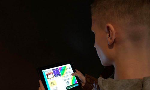 Kuvassa nuoren miehen kuva otettuna hänen olkansa takaa. Lyhyt vaalea tukka- iPadista selailee nettisvuja.