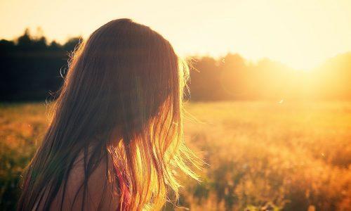 Kuvassa nuori tyttö kulkee auringon valaisemalla pellolla.