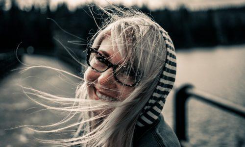 Kuvassa nuori tyttö hymyilee kameraan sillalla ja tuuli heiluttaa hänen vaaleita hiuksiaan.