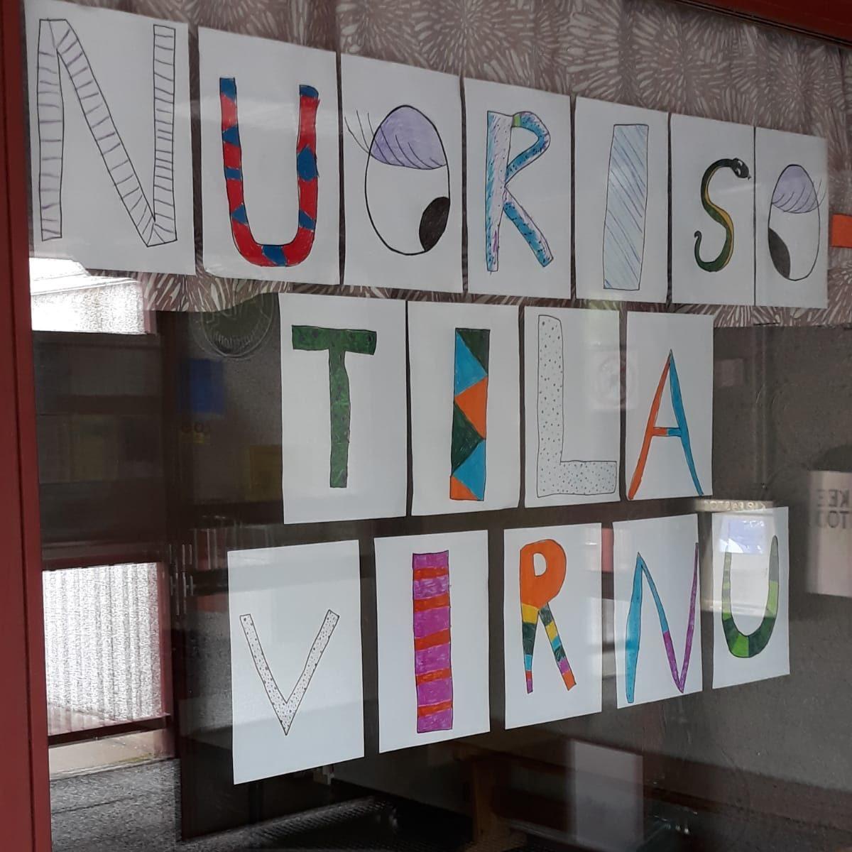 """Nuorisotila Virnun ikkuna. Lapset piirtäneet erilaisilla väreillä kirjain kirjaimelta kyltin """"Nuorisotila Virnu""""."""