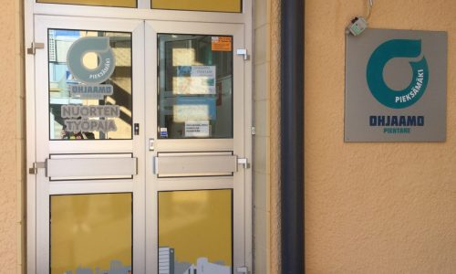 Ohjaamo Pieksämäen, nuorten työpajan ja kaupungin työllisyyspalveluiden ulko-ovi. Keltaiset teippaukset ovessa, seinässä sininen iso ohjaamon logo,