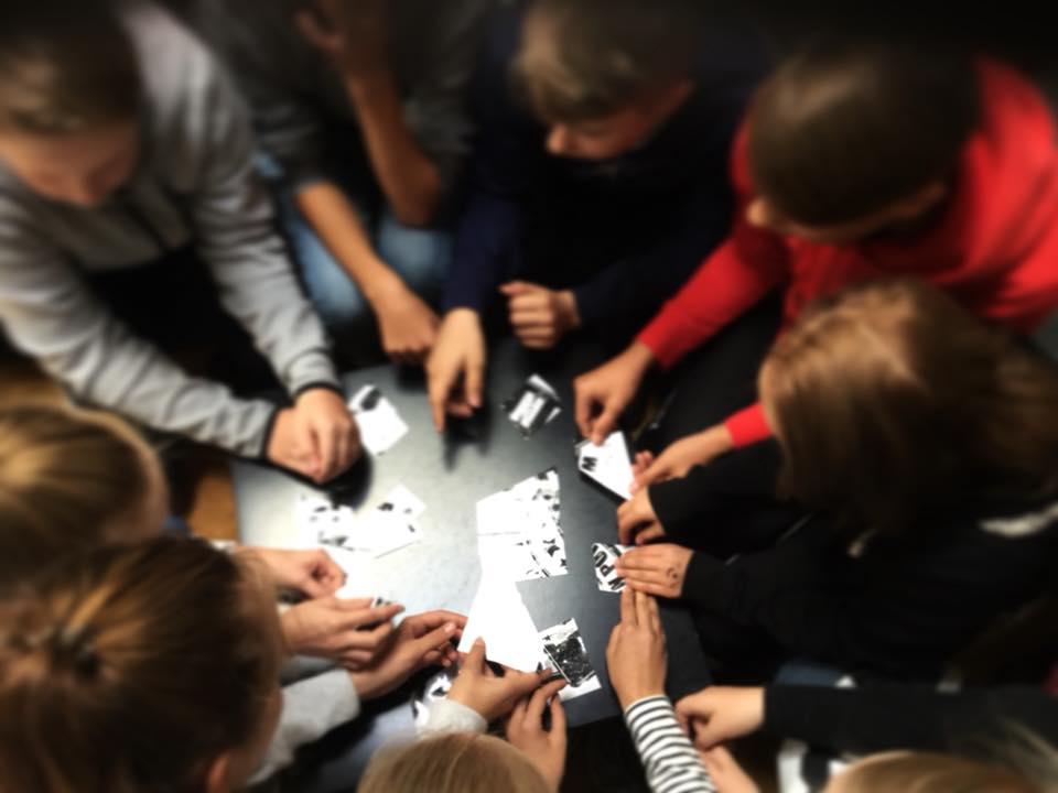 Kuvassa nuoria pöydän ympärillä, useita käsiä touhuamassa yhdessä Po1nt palapelin äärellä.