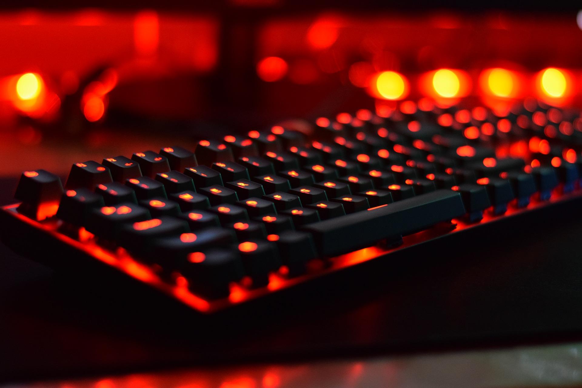 Kuvassa tietokoneen näppäimistö, joka on valaistu punaisilla valoilla.