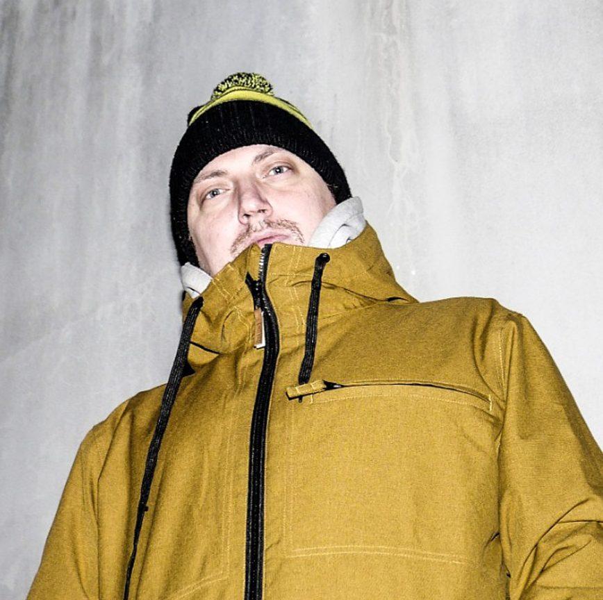 Kuvassa Tapani kansalainen. Keltainen takki,. musta pipo. Vaalea aikuinen mies jolla viikset