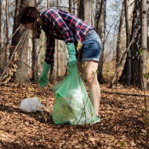 Kuvassa nainen keräämässä roskia metsästä.