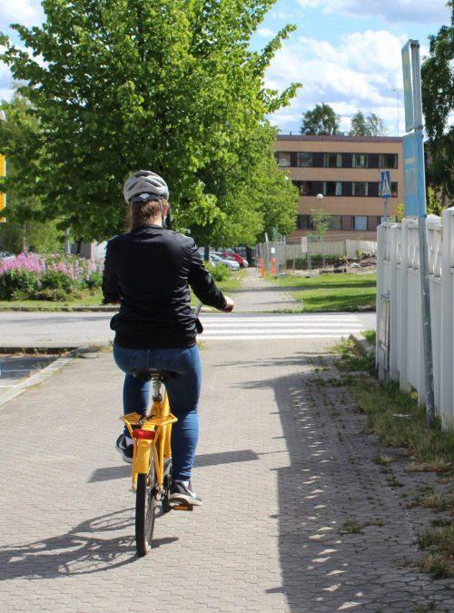 Tyttö pyöräilee kadulla pyöräilykypärä päässään.