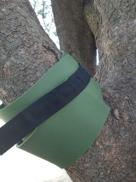 Puunoksa, johon kiinnitetty riippumaton köysi ja puuta on suojattu retkipatjan suikaleella.